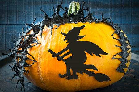 original idea: Idea homemade decorating for Halloween. Application: barbed tape made of black crepe paper and a witch on pumpkin. The original design in the style of Halloween. Tinted photo