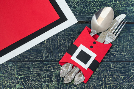 Creating a festive decoration for the table setting for Christmas in the shape of jacket Santa Claus. Step by step photo instructions. Step 5. Cutlery in a case in the shape of jacket Santa Claus Stock Photo
