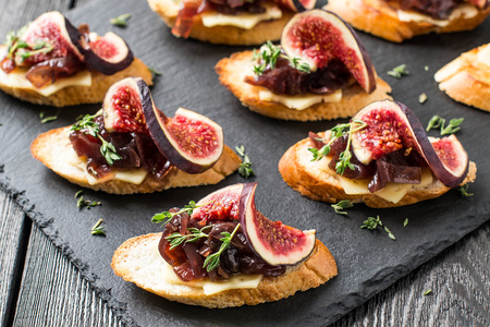 Canape or crostini with toasted baguette, cheese, onion jam, figs and fresh thyme on a slate board. Delicious appetizer, ideal as an aperitif. Selective focus Stock Photo