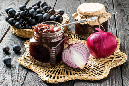 Red onion jam (onion confiture) with grapes in glass jars and ingredients for its preparation on a straw napkin and a wooden table. French cuisine. Selective focus Stok Fotoğraf - 64302097