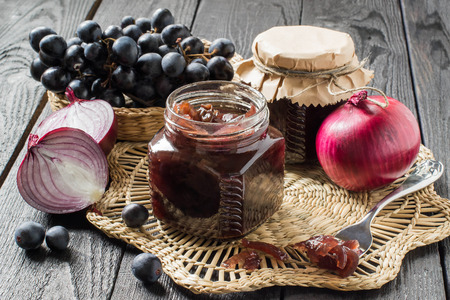 Red onion jam (onion confiture) with grapes in glass jars and ingredients for its preparation on a straw napkin and a wooden table. French cuisine. Selective focus Stock Photo