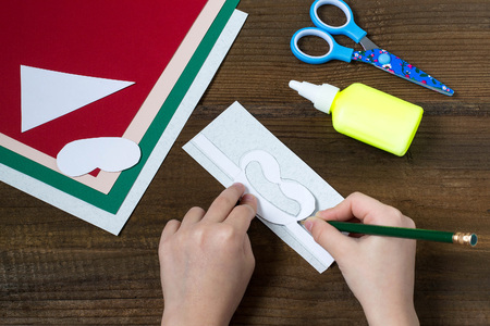 dint: Creating a Christmas decoration for table setting. Decor for serviette in form of Santa Claus. Children project, step by step photo instructions. Step 2. Drawing details by dint of templates Stock Photo