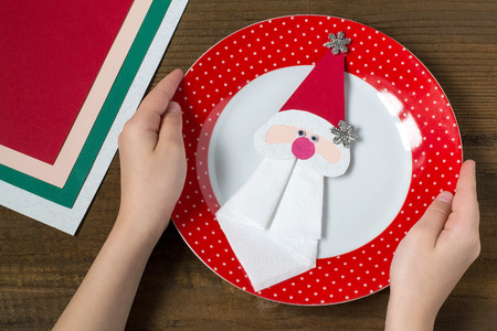 servilleta de papel: Creating a Christmas decoration for table setting. Decor for serviette in form of Santa Claus. Children project, step by step photo instructions. Step 10. Decor for serviette on a plate Foto de archivo