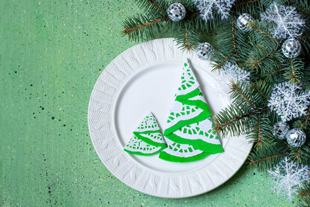 servilleta de papel: The idea of Christmas decoration for the table setting. Homemade decor for serviette in the form of a Christmas tree on a plate. Decorated Christmas tree branch on a green background