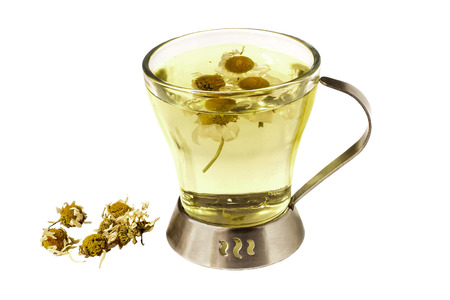 Useful herbal tea with dried chamomile Matricaria chamomilla isolated on white background. Used in healthy nutrition and herbal medicine Stock Photo