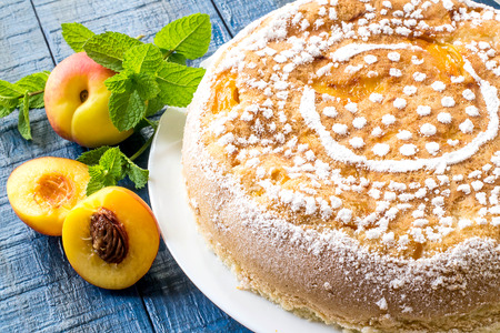 Delicious homemade cake with nectarines on a blue wooden table. Selective focus
