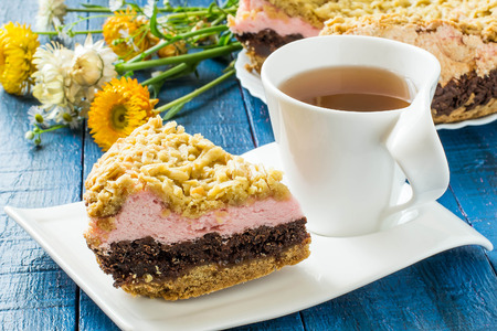 multilayer: Baking in multicooker. Homemade festive multilayer cake with jam, chocolate, marshmallows, streusel and a cup of tea on a blue wooden background. Selective focus Stock Photo