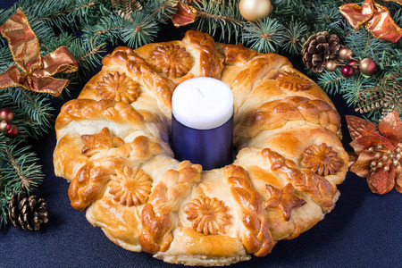 Creative homemade cake of yeast dough filled with cheese. The original festive cake in the form of a Christmas wreath on the background of branch Christmas tree with decoration on a blue background