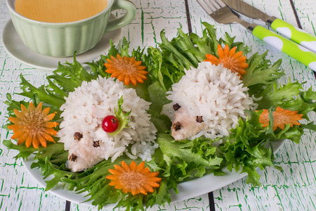 Healthy childrens dinner. Creative idea: meatballs of turkey meat and rice steamed in the form of funny hedgehogs. Served on lettuce leaves with fresh vegetables