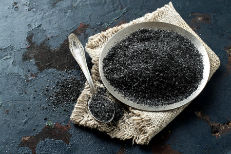Special useful Kostroma black salt (Russia) in metal plate on dark background. Prepared according to an ancient recipe on Thursday before the Orthodox Easter. Baked in an oven with useful additives