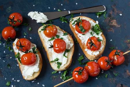 Crostini met geroosterde stokbrood, kaas en gegrilde cherry tomaten op een oude blauwe gestructureerde achtergrond. Tomaten gekookt met olijfolie, knoflook, zout en peper Stockfoto