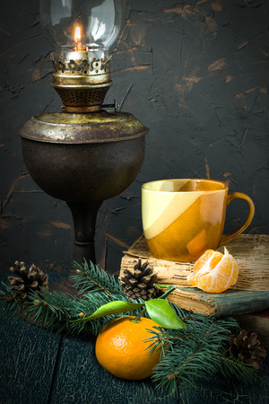 Vintage Christmas atmosphere: burning kerosene lamp, old books, spruce branches with cones, tangerines. Vintage style. Selective focus, toned photo
