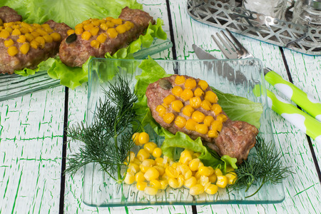 forcemeat: Healthy child food. Creative idea: rissole of forcemeat decorated with corn as a goldfish. Served on lettuce leaves with fresh vegetables