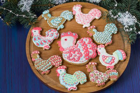 Homemade creative Christmas baking. Painted gingerbread cookies with icing in the shape of rooster on background decorated with fir branches. Rooster � symbol of new year 2017 on the eastern calendar Stock Photo