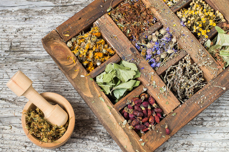 Gedroogde medicinale plant in een oude houten kist (kamille, tansy, linde, sint-janskruid, korenbloem, toorts, calendula, aalbessenblad, rozenbottel). Gebruikt voor de bereiding van gezonde dranken, afkooksels Stockfoto