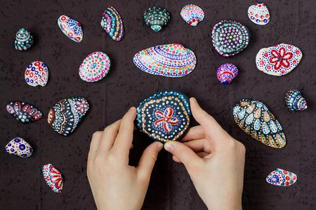 Met de hand geschilderde kleurrijke dot patronen op zee kiezels en schelpen. Children's kunstproject, een ambacht voor kinderen. DIY concept. Stap voor stap foto instructies. Stap 5. Het resultaat van de schilderkunst Stockfoto