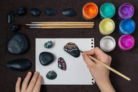 Met de hand geschilderde kleurrijke puntpatronen op overzeese kiezelstenen en shells. Kunstproject voor kinderen, een ambacht voor kinderen. DIY-concept. Stap voor stap foto-instructies. Stap 4. Handgeschilderde stippatronen