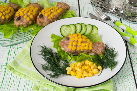 Healthy child food. Creative idea: rissole of forcemeat decorated with corn as a goldfish. Served on lettuce leaves with fresh vegetables