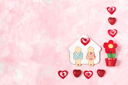 Festive composition to Valentines Day. Symbol of love and fidelity - hand-painted wooden house with little man, flower and hearts on a pink textured background with space for text. Flat lay, top view Reklamní fotografie