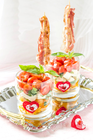 Festive verrines with grilled bacon on skewers. Original feed caprese salad in a glass. Serving for the holidays: Valentines Day, birthday, Mothers Day. Selective focus, vertical Reklamní fotografie