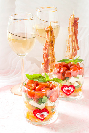 Festive verrines with grilled bacon on skewers. Original feed caprese salad in a glass. Serving for the holidays: Valentines Day, birthday, Mothers Day. Selective focus, vertical Stock Photo