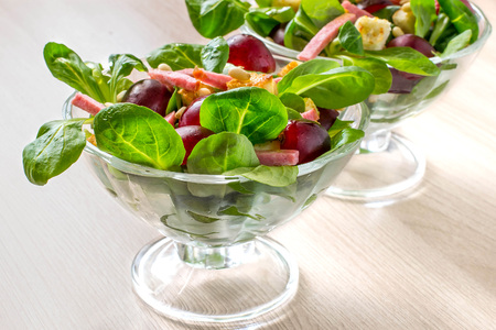 Delicious salad with fresh corn salad, grapes, sausage, croutons and nuts Siberian pine in glass vases
