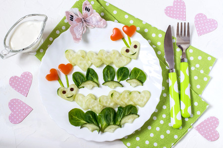 Creative idea of food decoration for Valentines Day. Fun loving caterpillars, carved in the shape of hearts of cucumber. Healthy and vegetarian food. Symbols of Valentines Day in the design