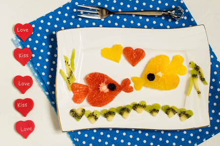 Creative idea of food decoration for Valentines Day. Fruit salad with citrus. Two kissing goldfish composed of hearts, cut from grapefruit, orange, kiwi. Symbols of Valentines Day in the design