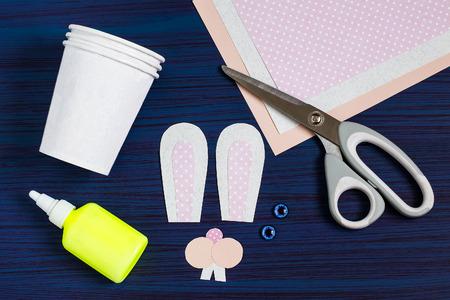 Zelfgemaakt maken van dozen uit papieren bekers voor snoep en snoep in de vorm van Pasen-haas. Aanwezige kinderen. DIY-concept. Stap voor stap foto-instructies. Stap 3. Details vastmaken