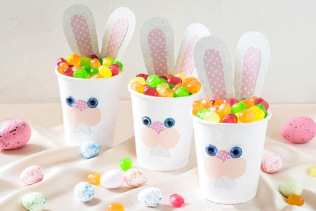 Paper cups in the form of funny Easter Bunny with candy. Homemade applique on paper cups. The idea for children gifts. DIY concept for the celebration of Easter Stock Photo