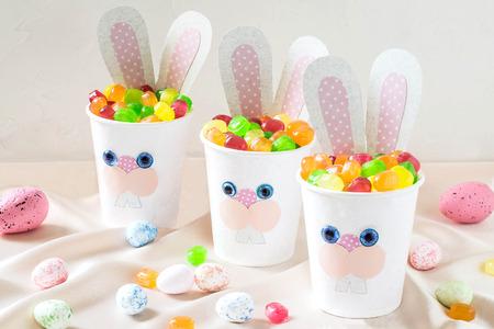 Papieren bekers in de vorm van grappige paashaas met snoep. Zelfgemaakte applique op papieren bekers. Het idee voor kindercadeaus. DIY-concept voor de viering van Pasen