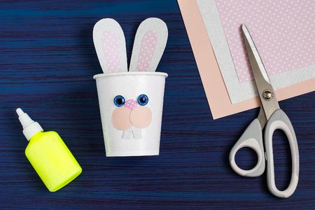 Zelfgemaakt maken van dozen uit papieren bekers voor snoep en snoep in de vorm van Pasen-haas. Aanwezige kinderen. DIY-concept. Stap voor stap foto-instructies. Stap 5. Neushoorns lijmen
