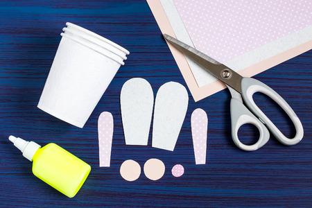 Zelfgemaakt maken van dozen uit papieren bekers voor snoep en snoep in de vorm van Pasen-haas. Aanwezige kinderen. DIY-concept. Stap voor stap foto-instructies. Stap 2. Details knippen