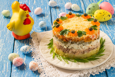 Multilayer festive salad with tuna, vegetables and eggs on a blue wooden table with eggs and chicken. Easter food, Easter recipe. Selective focus