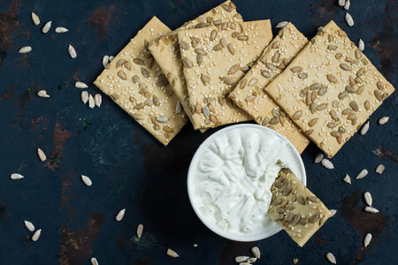 sesame cracker: Homemade wholegrain crackers with sesame, sunflower seeds and cream cheese with fresh herbs on the old blue textured background. The concept of diet and healthy eating. Top view