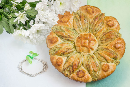 Creative homemade cake of yeast dough with stuffed of cottage cheese. The original cake in shape of flower and card for your text. Festive dessert for Mothers Day, birthday, anniversary. Top view