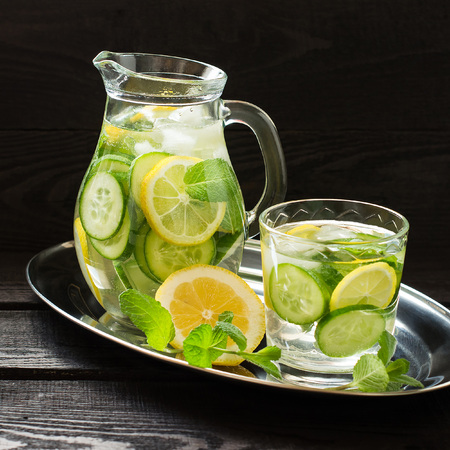 Water Sassi. Vitaminized cleansing water with lemon, cucumber, ginger, mint and ice in a pitcher and a glass on a metal tray. The concept of dietary and vegetarian nutrition. Square image Stock Photo