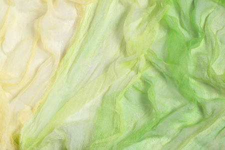 Bright background of crumpled gauze painted yellow-green shades. Used in design for decor