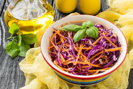 Fresh vitamin salad of red cabbage (scotch kale) with carrot and basil on a dark wooden background. It is used in dietary and vegetarian food, as well as for the prevention of cardiovascular diseases
