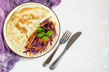 Delicious and healthy breakfast of omelette and salad of red cabbage (scotch kale) with carrots and basil Lizenzfreie Bilder