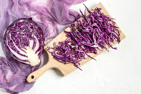Chopped scotch kale or red cabbage on a cutting board and half of cabbage head on gauze napkin. It is used in dietary and vegetarian nutrition, as well as for the prevention of cardiovascular disease Lizenzfreie Bilder