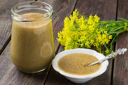 Homemade mustard with grains in jar and gravy boat, mustard flowers on old wooden table. Spicy seasoning for various dishes. Selective focus