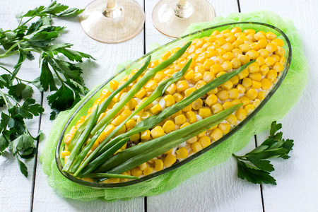 Delicious festive salad with eggs, cheese, prunes and canned corn. The original form of an ear of corn. Creative idea for holiday meals