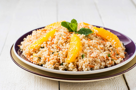 Fresh salad of crumbly couscous with carrots, orange and mint in a bowl closeup on white wooden table. Dietary vegetarian food traditional Mediterranean cuisine, recipes. Selective focus