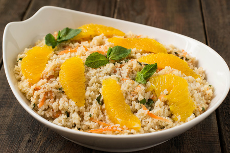 Useful fresh salad of crumbly couscous with carrots, orange and mint in a bowl closeup on a wooden table. Lizenzfreie Bilder
