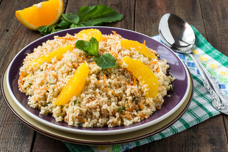 Useful fresh salad of crumbly couscous with carrots, orange and mint on a purple plate on wooden table.