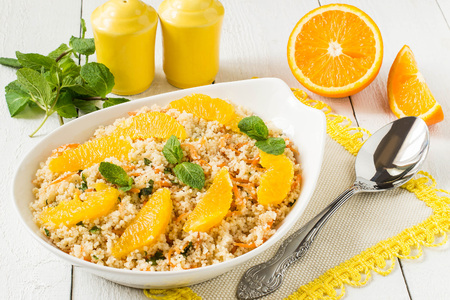 Useful fresh salad of crumbly couscous with carrots, orange and mint. Dietary vegetarian food traditional Mediterranean cuisine, recipes. Selective focus Lizenzfreie Bilder
