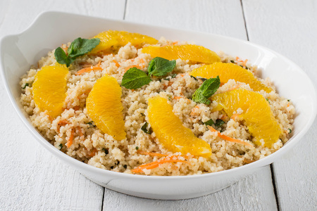 Useful fresh salad of crumbly couscous with carrots, orange and mint in a bowl closeup on white wooden table.