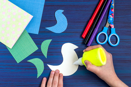 Making a greeting card for Mothers Day. Childrens art project. DIY concept. Step-by-step photo instruction. Step 5. Application of glue to the detail of image