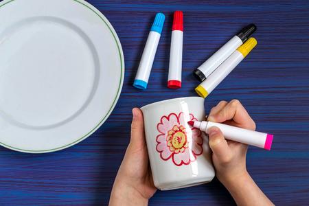 Handgemaakt kleurrijk schilderij op borden voor aardewerk. Kunstproject voor kinderen, handwerk voor kinderen. DIY-concept. Stapsgewijze foto-instructies. Stap 3. Tekenen en kleuren van bloembladen Stockfoto